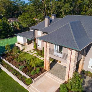 Imagen de fachada de casa marrón, actual, extra grande, de dos plantas, con revestimiento de hormigón, tejado a dos aguas y tejado de varios materiales