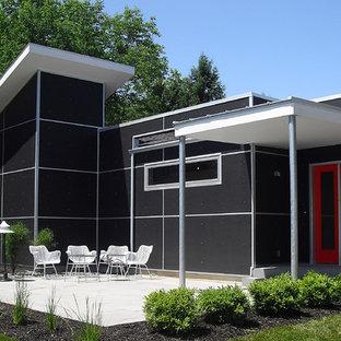Ejemplo de fachada de casa negra, urbana, de tamaño medio, de una planta, con tejado plano