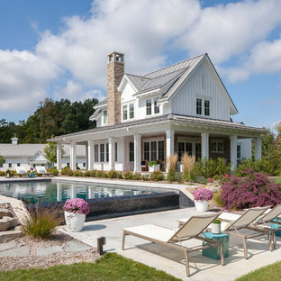Inspiration for a huge farmhouse white two-story wood exterior home remodel in Grand Rapids with a metal roof