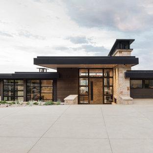 Immagine della facciata di una casa unifamiliare grande marrone contemporanea a due piani con rivestimento in legno, tetto piano e copertura in metallo o lamiera