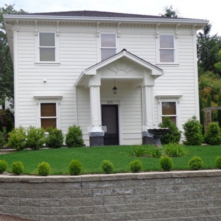 Example of a small classic white two-story concrete exterior home design in Denver with a hip roof
