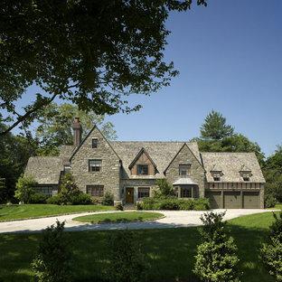 Immagine della facciata di una casa classica con rivestimento in pietra e tetto a capanna