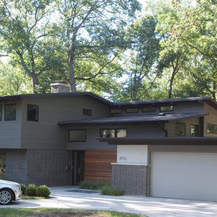 Example of a large midcentury modern gray two-story mixed siding flat roof design in Chicago