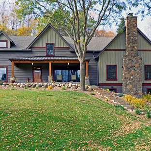Modelo de fachada verde, de estilo de casa de campo, de tamaño medio, de dos plantas, con tejado a dos aguas y revestimiento de madera