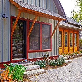 Modelo de fachada verde, campestre, de tamaño medio, de dos plantas, con tejado a dos aguas y revestimiento de madera
