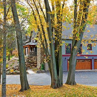 Imagen de fachada verde, campestre, de tamaño medio, de dos plantas, con tejado a dos aguas y revestimiento de madera