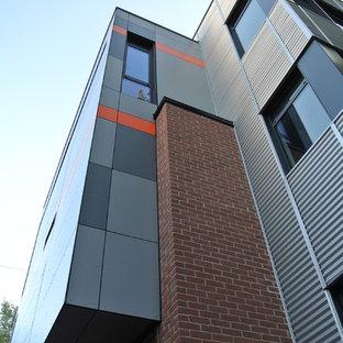 Imagen de fachada bohemia, de tres plantas, con revestimiento de metal y tejado plano