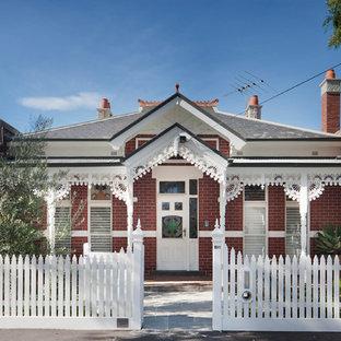 Foto de fachada de casa roja, clásica, de tamaño medio, de dos plantas, con revestimiento de ladrillo, tejado a cuatro aguas y tejado de varios materiales
