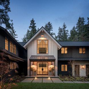 Foto de fachada de casa multicolor, campestre, de dos plantas, con revestimientos combinados, tejado a dos aguas y tejado de teja de madera