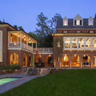 Large elegant red two-story brick house exterior photo in DC Metro with a hip roof and a shingle roof