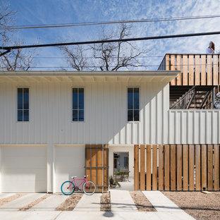 На фото: двухэтажный, деревянный, белый многоквартирный дом в стиле неоклассика (современная классика) с плоской крышей