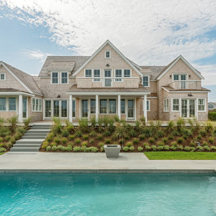 Coastal beige two-story wood exterior home idea in Other with a shingle roof