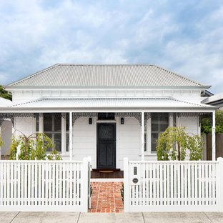 Mid-sized traditional one-storey white house exterior in Melbourne with wood siding, a hip roof and a metal roof.