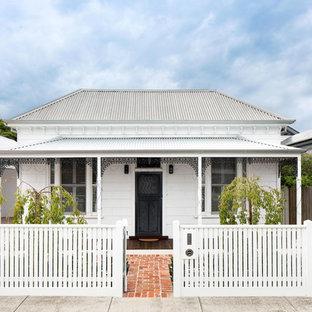 Modelo de fachada de casa blanca, clásica, de tamaño medio, de una planta, con revestimiento de madera, tejado a cuatro aguas y tejado de metal