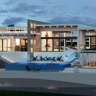 Diseño de fachada blanca, moderna, grande, a niveles, con revestimiento de estuco y tejado plano
