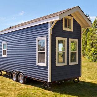Ejemplo de fachada azul, marinera, pequeña, de una planta, con revestimiento de madera y tejado a dos aguas