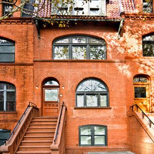 Diseño de fachada de piso naranja, de estilo americano, de tamaño medio, de tres plantas, con revestimiento de ladrillo y tejado de teja de madera