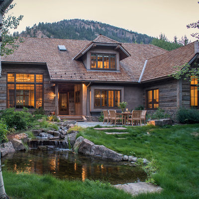 Mountain style brown wood exterior home photo in Other with a clipped gable roof