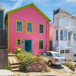 Modelo de fachada de casa rosa, ecléctica, de tamaño medio, de tres plantas, con revestimiento de madera, tejado a dos aguas y tejado de teja de madera