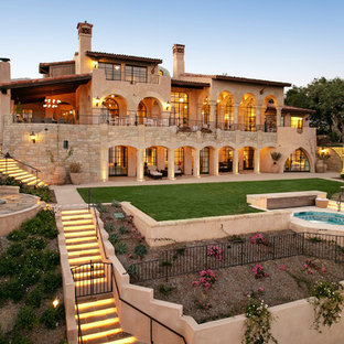 Example of a large tuscan beige three-story stone house exterior design in Santa Barbara with a shed roof and a tile roof