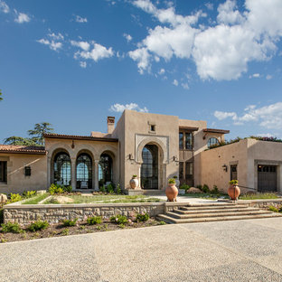 Example of a large tuscan beige two-story stone exterior home design in Santa Barbara with a tile roof