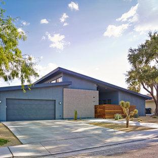 Inspiration för ett mellanstort 60 tals blått hus, med allt i ett plan, stuckatur och pulpettak