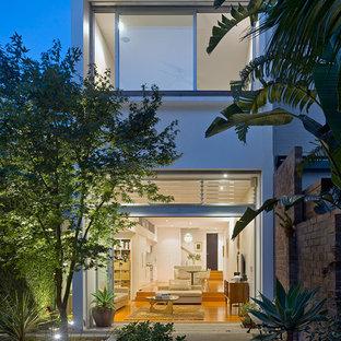 Ejemplo de fachada de casa blanca, contemporánea, pequeña, de dos plantas, con revestimiento de ladrillo, tejado plano y tejado de metal