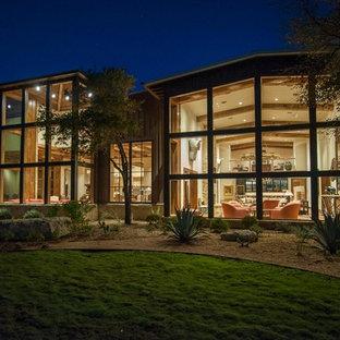 Ejemplo de fachada blanca, campestre, extra grande, de una planta, con revestimiento de vidrio y tejado a dos aguas