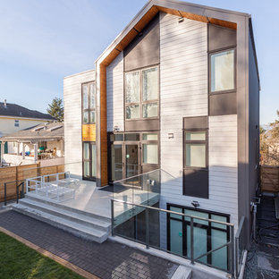 Large minimalist white three-story mixed siding exterior home photo in Vancouver with a metal roof