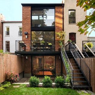 Imagen de fachada de casa pareada contemporánea, de tres plantas, con revestimiento de ladrillo