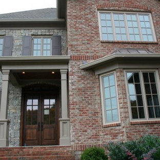 Inspiration for a large gray two-story stone gable roof remodel in Nashville