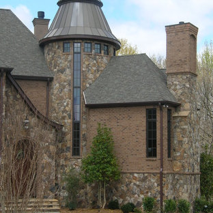 Example of a large 1950s brown two-story stone exterior home design in Charlotte