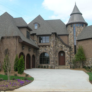 Example of a large midcentury modern brown two-story stone exterior home design in Charlotte
