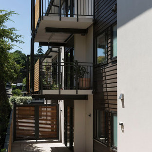 Contemporary grey apartment exterior in Auckland with concrete fiberboard siding and a flat roof.