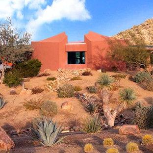 Ejemplo de fachada de casa naranja, contemporánea, pequeña, de dos plantas, con revestimiento de estuco, tejado plano y techo verde