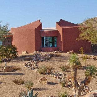 Imagen de fachada de casa naranja, contemporánea, pequeña, de dos plantas, con revestimiento de estuco, tejado plano y techo verde