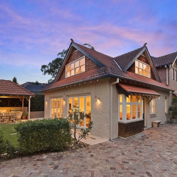 Inspiration for a large timeless beige two-story stucco gable roof remodel in Sydney