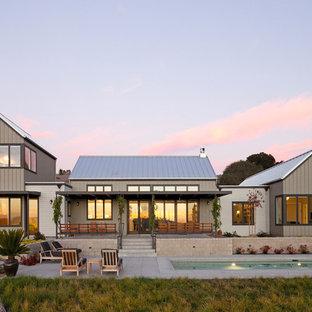 Esempio della facciata di una casa grigia country a due piani con tetto a capanna e copertura in metallo o lamiera