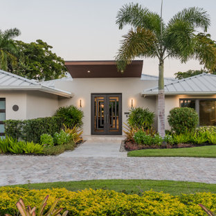 Example of an island style white one-story house exterior design in Miami with a hip roof and a metal roof