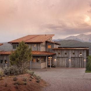 Réalisation d'une façade de maison marron champêtre de taille moyenne et à un étage avec un revêtement mixte, un toit en appentis et un toit en métal.