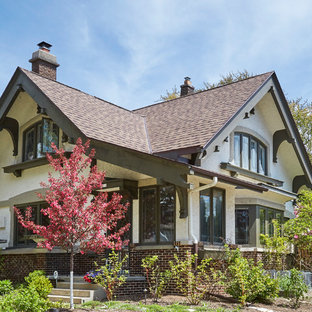 Mid-sized arts and crafts beige two-story stucco exterior home photo in Milwaukee with a shingle roof