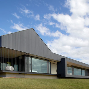 Contemporary one-storey black house exterior in Other with a flat roof.