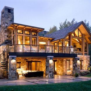 Exempel på ett stort rustikt brunt stenhus