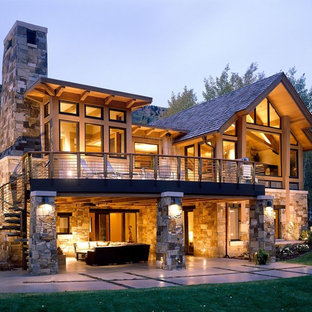 Large rustic brown stone exterior home idea in Denver