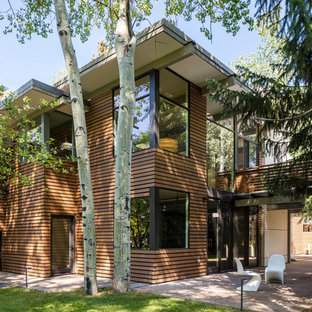 Large midcentury modern two-story wood exterior home idea in Denver with a mixed material roof