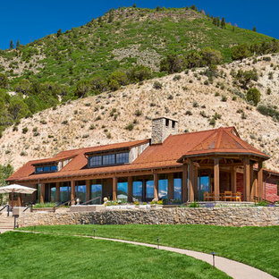 Example of a large mountain style red wood exterior home design in Denver with a metal roof