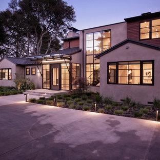 Imagen de fachada de casa multicolor, minimalista, grande, de dos plantas, con revestimientos combinados, tejado a dos aguas y tejado de metal