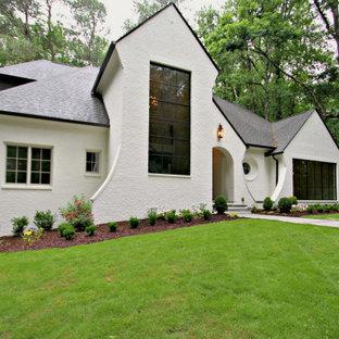 На фото: большой, трехэтажный, белый частный загородный дом в стиле современная классика с облицовкой из крашеного кирпича, двускатной крышей и крышей из гибкой черепицы