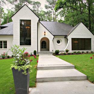Aménagement d'une grand façade de maison blanche classique à deux étages et plus et en briques peintes avec un toit à deux pans et un toit en shingle.