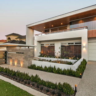 Inspiration for a contemporary two-storey stucco beige house exterior in Perth with a flat roof.